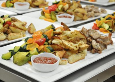 Mix of meat served with potatoes and grilled vegetables